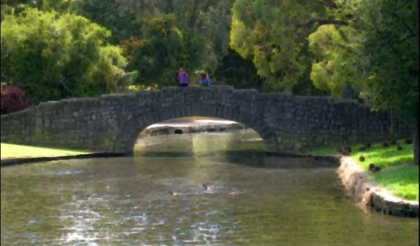 Old stone bridge across the river with two people on it.