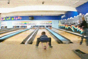 A boy throwing a bowling ball down the lane