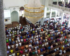 People sitting in a prayer hall for Friday Prayer.