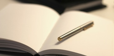 A pen resting on a blank piece of paper