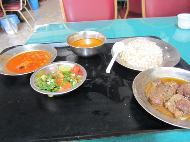 A platter with bowls of rice, meat, salad, beans and soup