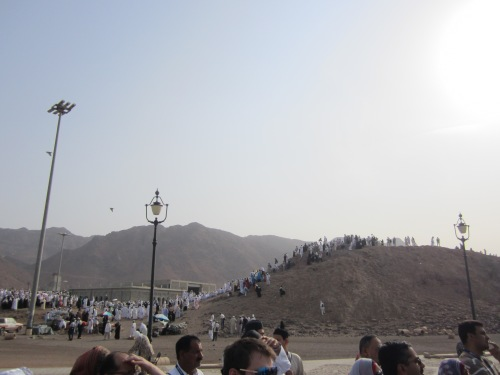 A small hill with people on it just in front of a row of red mountains