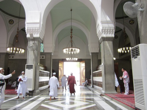 A person walking out the door of Masjid Quba