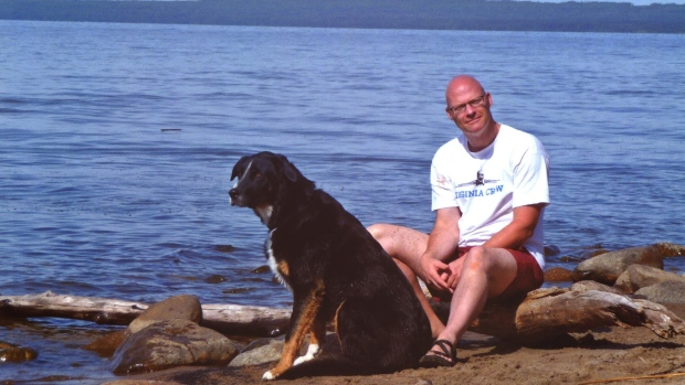 A man sitting on the beach with a large, black and brown dog.