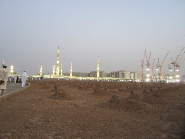 A field of burial mounds, with a small pathway to the left and the Prophet's Mosque in the distance.