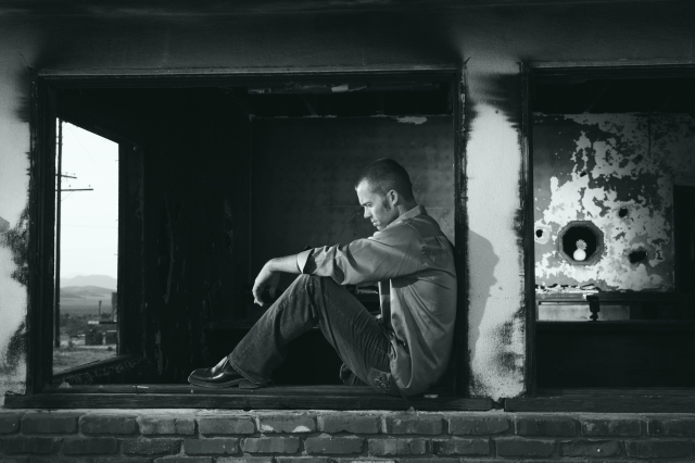 A black and white photo of a man sitting on a ruined windowsill, looking deep in thought.
