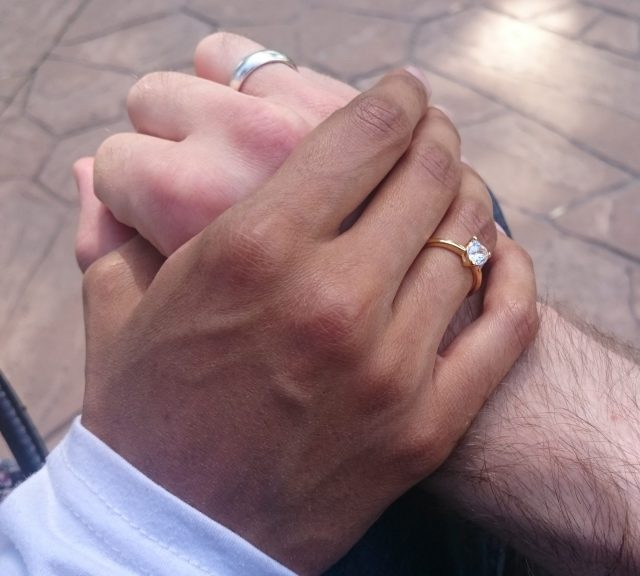 A hand of a woman with brown skin, wearing a wedding ring, holds the hand of a white man, wearing a wedding band.